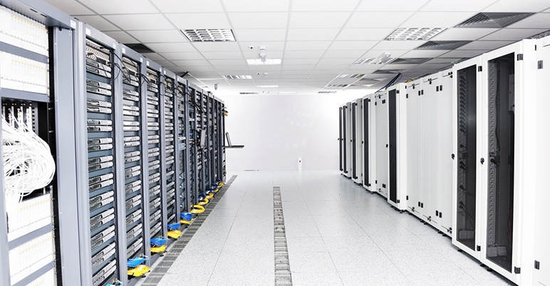 Image of data center with servers and air units in the ceiling.