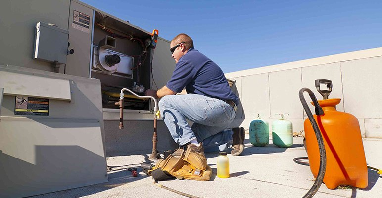 HVAC technician performing HVAC maintenance
